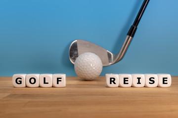 """Würfel bilden die Worte """"GOLF"""" und """"REISE"""" vor einem Golfball und einem Golfschläger"""