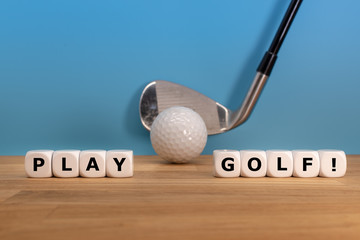 """Dice form the words """"PLAY GOLF!"""" in front of a golf ball and a driver."""