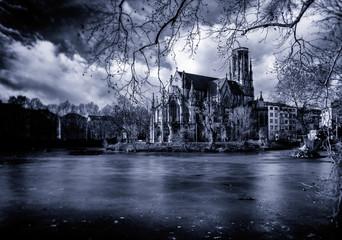 An old church behind a frozen lake