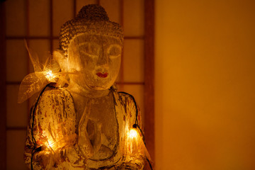 Buddha statue in warm light in interior with copy space, mystical and cozy