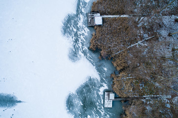 Aerial view of winter frozen lake with wooden houses on pier