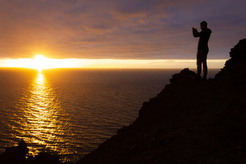 Photographer with cellphone standing on cliff edge rock capturing beautiful sunset by the sea in Gran Canaria. Silhouette of man taking photo with smartphone at twilight. Travel memories concept