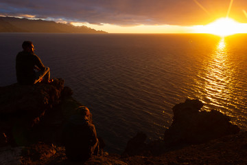 Couple of friends sitting on cliff edge rock staring at sunset by the sea in Gran Canaria, Spain. Young men contemplating twilight with sun reflecting on calm ocean. Travel destination concept