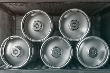 Metal beer kegs lie in a row