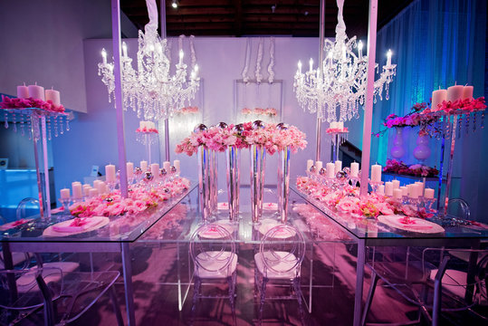 High end wedding tablescape with pillar candles and pink orchids and chandelier