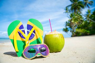 Aluminium Prints Carnaval Brazil flag flip-flops and brightly sequined carnival mask resting together in the sand on the shore of a palm-fringed Brazilian beach