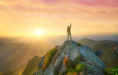 Silhouette of a champion on mountain top. Travel and adventure. Mountain hiking. Mountains during sunrise. Success and goal achievement. People success-image