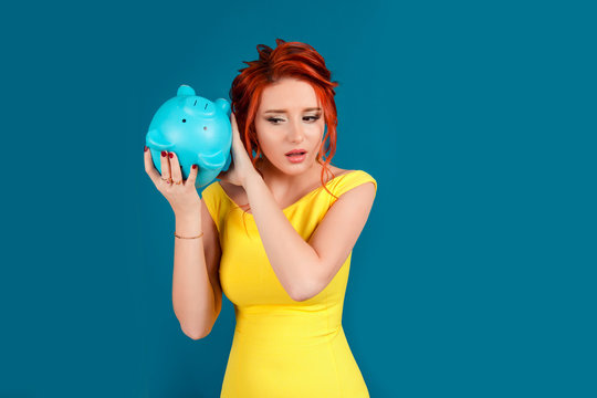 worried woman with empty piggy bank
