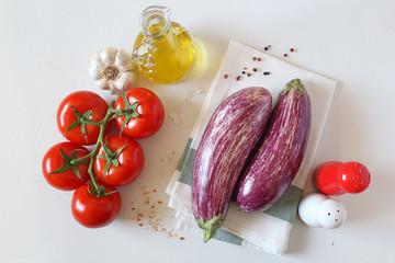 Raw graffiti eggplants, garlic, tomatoes  on light background