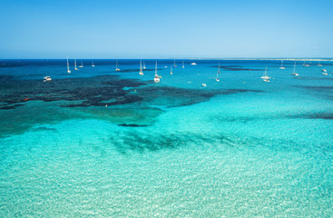Aerial view of boats and luxury yachts in transparent sea at sunny bright day. Summer seascape. Tropical landscape with lagoon, boats, azure water, sandy beach, blue sky. Top view from drone. Travel