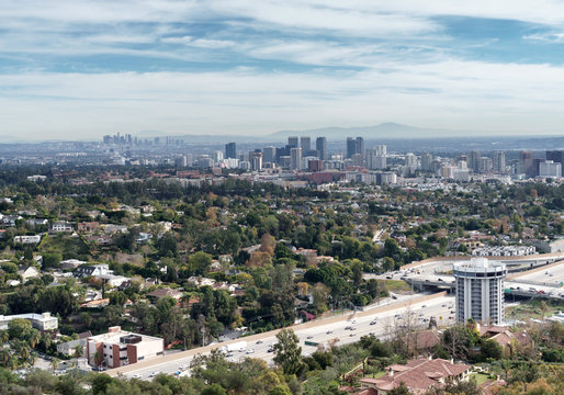 Aerial view of Los Angeles, California looking over the 405 freeway. Tall buildings and hills in background. Blue sky and clouds..