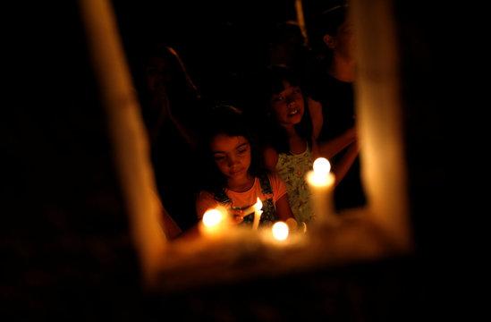 Children light candles during a vigil following the Vale dam burst in Brazil