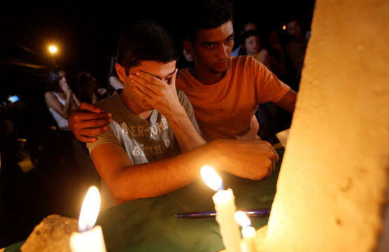 People light candles during a vigil following the Vale dam burst in Brazil