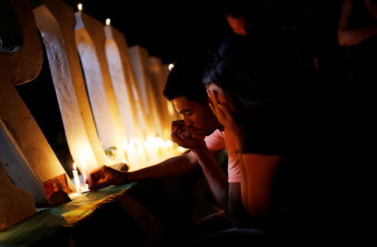 People react as they light candles during a vigil following the Vale dam burst in Brazil