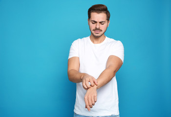 Young man scratching arm on color background. Annoying itch Wall mural