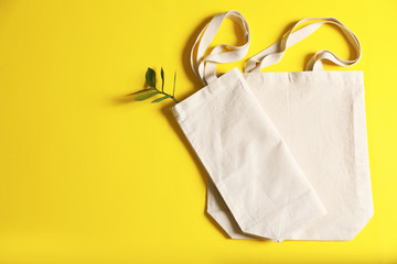 Flat lay composition with eco tote bags and space for text on color background