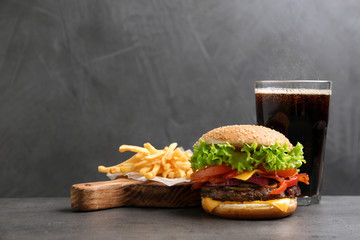 Burger with bacon, soda drink and french fries on table against grey background, space for text