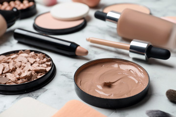 Composition with skin foundation, powder and beauty accessories on marble background
