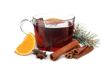 Composition with glass cup of mulled wine, cinnamon, orange and fir branch on white background