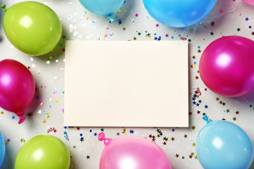 Flat lay composition of balloons and empty card with space for text on color background