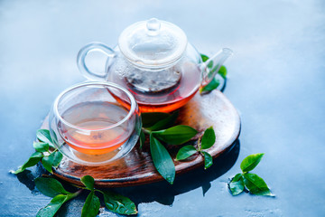 Teapot and double wall glass with tea leaves and a wooden coaster on a light blue background. Hot drink header with copy space.