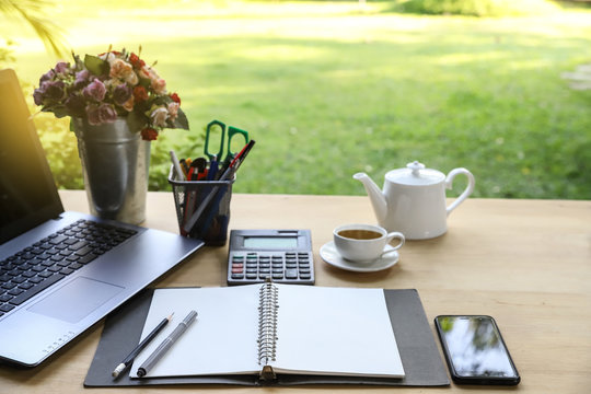 Wood table office outdoor with note book ,pen, smartphone,computer business, calculator and cup of tea on green garden background -image
