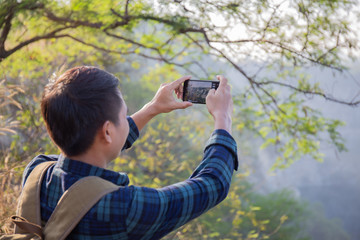 Asian male travelers are using a smartphone to take pictures of beautiful scenery.