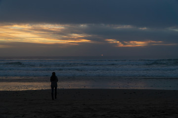 Woman taking pictures of the sunset on the Oregon coast