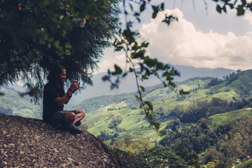 Young male photographer taking pictures of beautiful valley in Malaysia Cameron Highlands