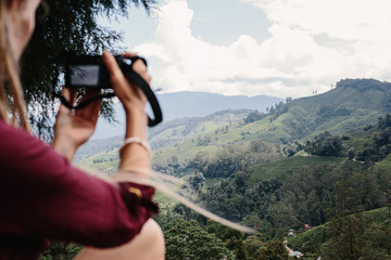 Young female photographer taking pictures of beautiful valley in Malaysia Cameron Highlands