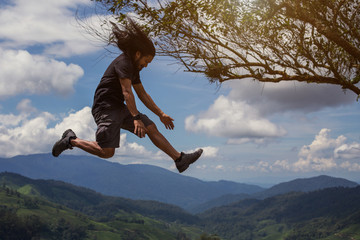 Happy traveler jumping above tropical mountains. Mixed race man portrait outdoor