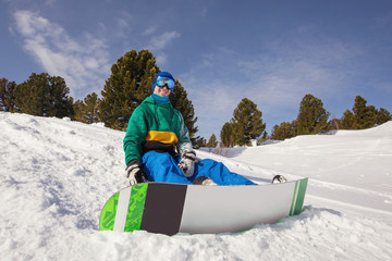 Snowboarder wearing snowboarding hoody sports gear posing with his snowboard looking away enjoying a sunny day at the mountains. Activities leisure lifestyle, winter sports concept