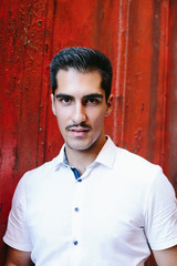 Portrait Of Young Handsome Man wearing moustache Outdoor on red wall background