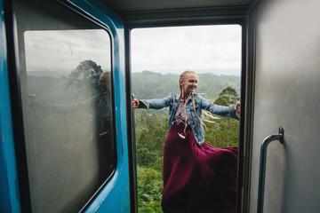 Female wearing beautiful dress travel by train in Sri Lanka