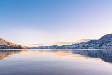Clear sky with sunset colors reflected in calm lake waters, with view of distant snow covered mountains