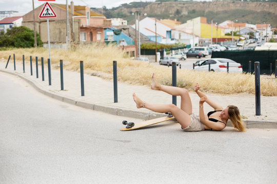 Young woman fall down with skate board on the street