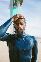 Portrait surfer man taking a shower on the beach outdoor. Mixed race dark skin and beard. Summer sport activity
