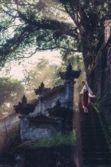 Woman walking in misty Bali temple. Fog and beautiful sunlight