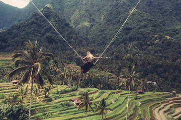 Woman on Swing between palm trees with beautiful rice terrace  landscape on background