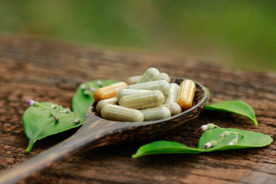herbal medicine in capsules for healthy eating with herb leaf, alternative supplement for good living lifestyle