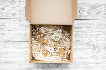 Order goods online concept. Cardboard box with gingerbread cookies on white wooden background top view space for text