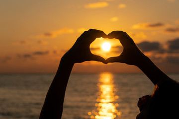Hands forming a heart shape with sunset silhouette near sea water, close up
