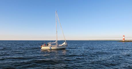 ein Segelboot segelt am Abend in den Hafen ein