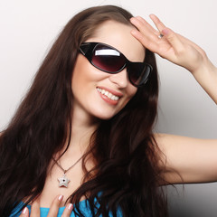brunette portrait with sunglasses over gray background