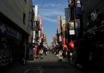 People walk on the street at a shopping and amusement district in Tokyo