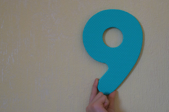 Hand holding blue number nine on mild yellow wall background with copy space for text. 9th anniversary birthday design or educational children toys for learning colors and numbers concept.