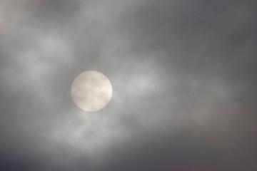 sun behind grey clouds