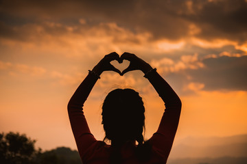 Women hands in the form of love and sunshine in the beautiful sky, the day of love, hands in the heart of love, love concept, heart-shaped hand gesture