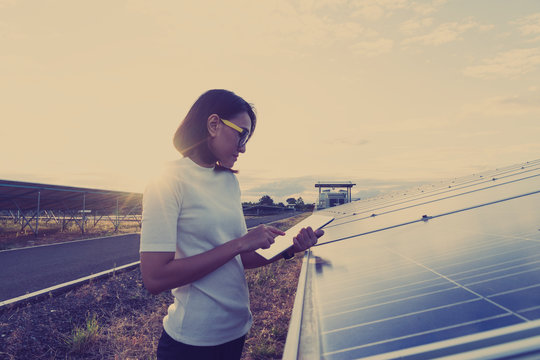 accountant auditor checking stock of asset at audit annual period with tablet checklist ; woman working on outdoor at solar power plant