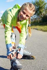 Roller skating girl in park rollerblading on inline skates.  Caucasian teenager in outdoor activities